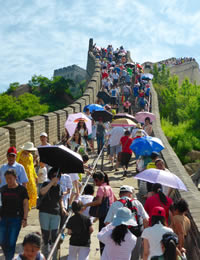 Sightseeers on the Great Wall, with umbrellas as sunshades